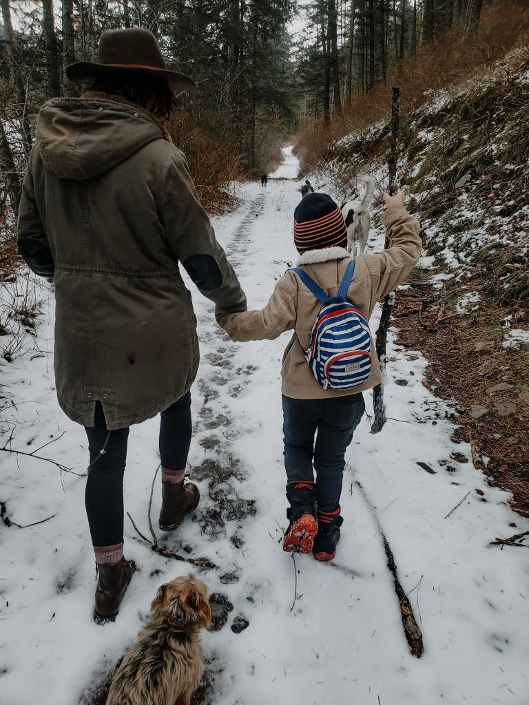 outdoor winter bucket list for kids- mom and son hiking through forest