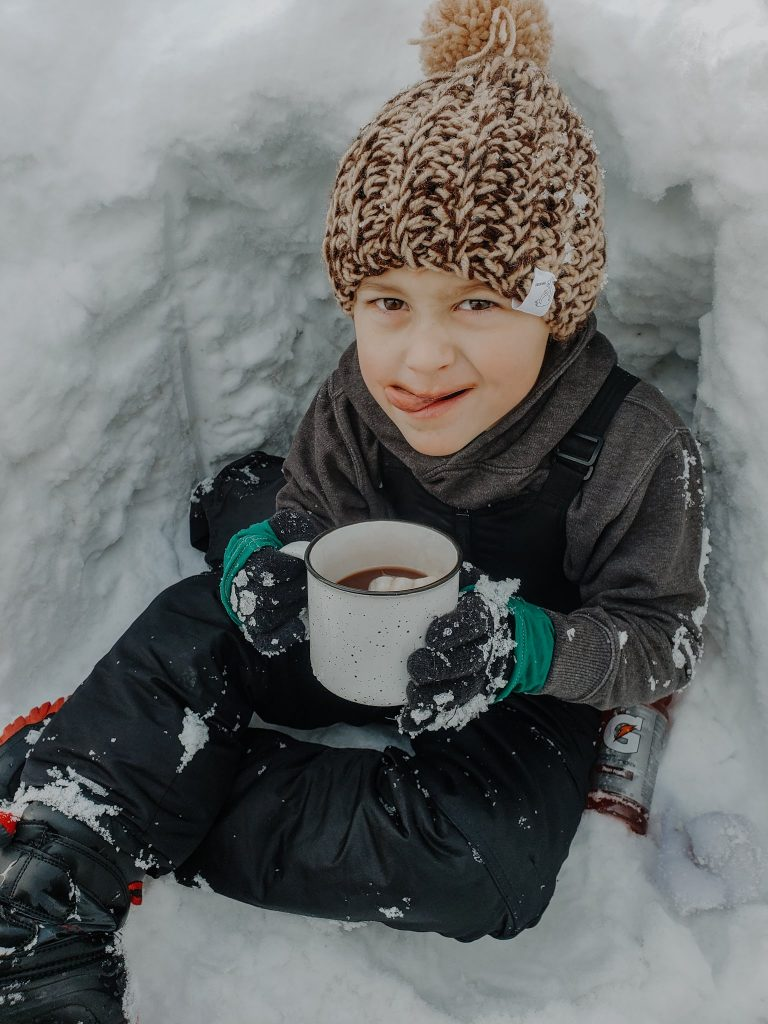 outdoor winter bucket list for kids- child sipping hot cocoa in igloo
